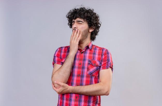 Сонный молодой симпатичный мужчина с вьющимися волосами в клетчатой рубашке, держащий руку во рту, зевает Бесплатные Фотографии