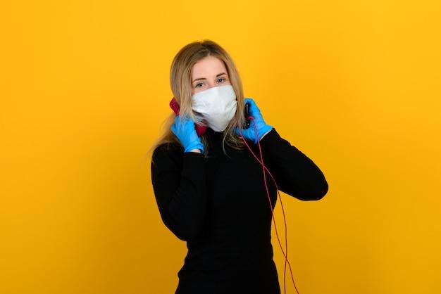 黒のボディスーツとウイルスからの医療マスクのほっそりした女の子のポーズ Premium写真