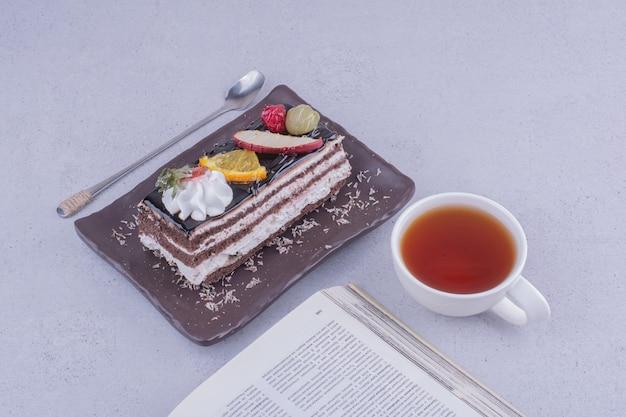 フルーツと一杯の飲み物が入ったチョコレートケーキのスライス。 無料写真