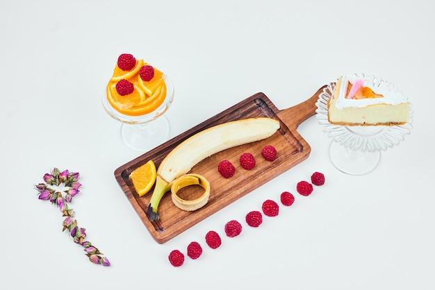 フルーツの盛り合わせを脇に置いたチーズケーキのスライス。 無料写真
