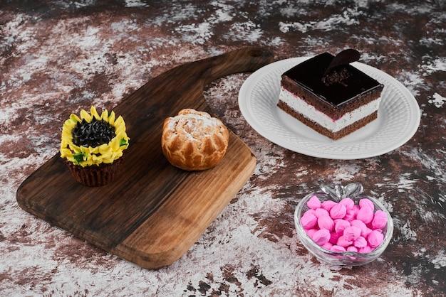 カップケーキと白いプレートにチョコレートチーズケーキのスライス。 無料写真