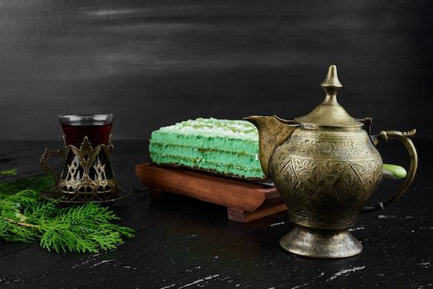 お茶のグラスと緑のケーキのスライス。 無料写真