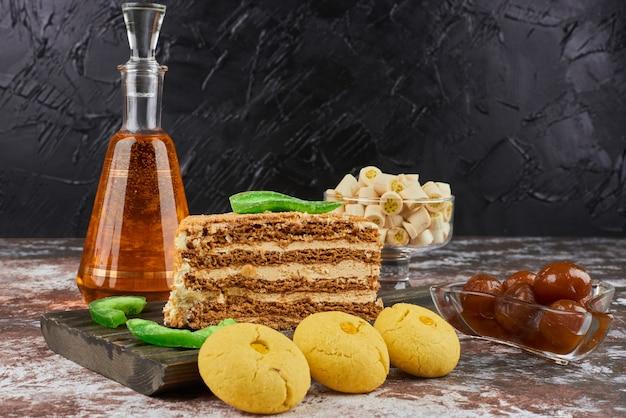 バタークッキーと飲み物のボトルと蜂蜜ケーキのスライス。 無料写真