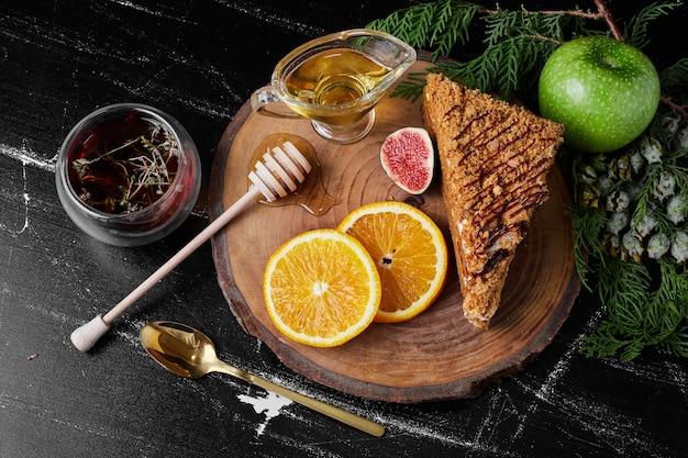 Кусочек медового торта с дольками апельсина и травяной чай. Бесплатные Фотографии