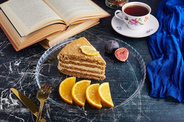 柑橘系の果物とお茶とメドビックケーキのスライス。 無料写真