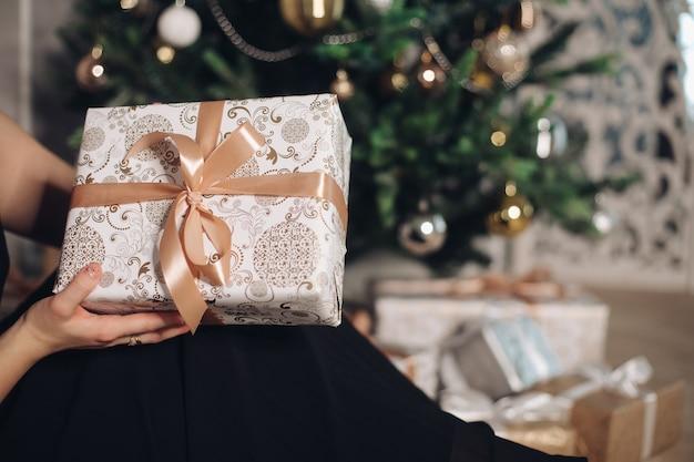 크리스마스 트리 앞에서 손에 새해 선물이 든 작은 상자 무료 사진