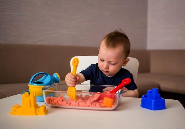Маленький мальчик играет с кинетическим песком за столом в комнате Premium Фотографии