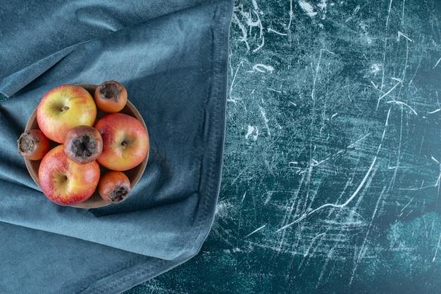 ボウル、タオル、青い背景にセイヨウカリンの果物とリンゴの小さな束。高品質の写真 無料写真