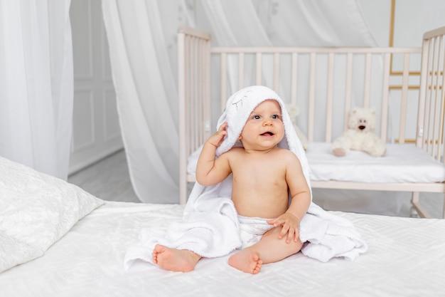Маленький ребенок мальчик 8 месяцев сидит в полотенце на белой кровати в легкой детской в подгузниках после купания Premium Фотографии