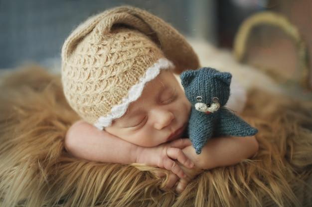 かごの中の小さな子供がポンポン付きの暖かいニット帽子で眠る Premium写真