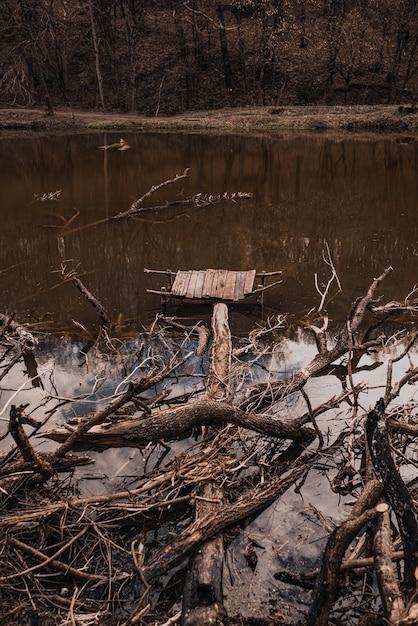 Небольшой старый деревянный разрушенный пирс на реке с выброшенными ветвями деревьев Premium Фотографии