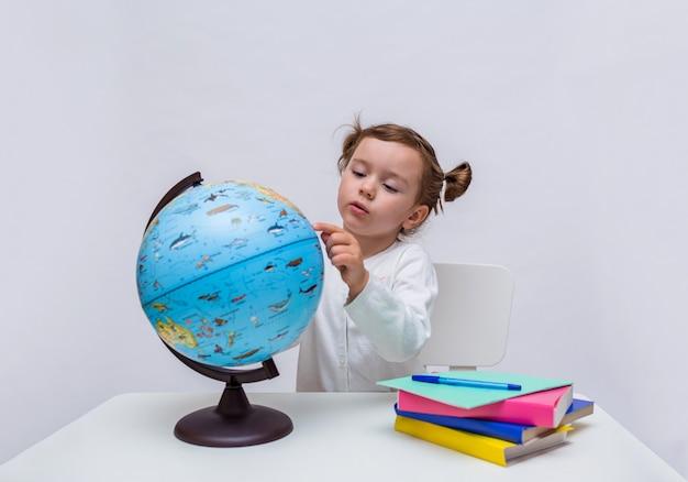 Маленькая школьница сидит с глобусом за столом на белом фоне изолированной Premium Фотографии