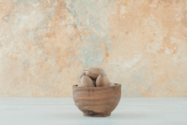 흰색 바탕에 견과류의 작은 나무 그릇. 고품질 사진 무료 사진
