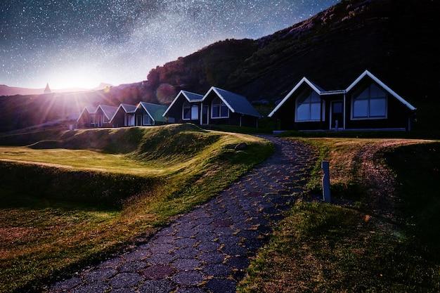 Небольшая деревянная церковь и кладбище хофскиркья хоф, скафтафетль исландия. живописный закат сквозь кроны деревьев Бесплатные Фотографии