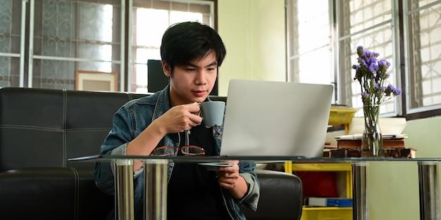 スマートな男は、仕事中にコンピューターのラップトップの前に座ってコーヒーを飲んでいます。 Premium写真