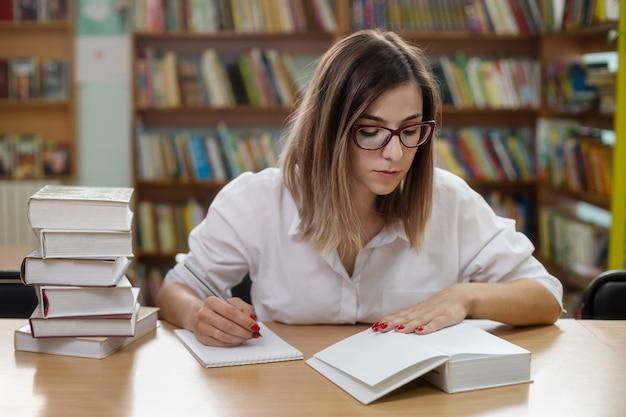 Умная женщина в очках учится в библиотеке с книгами Premium Фотографии