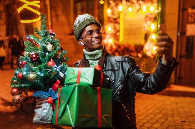 Улыбающийся афроамериканец с елкой и подарками в руках делает селфи на улице Premium Фотографии