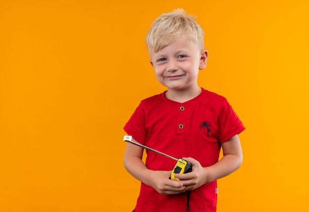 Улыбающийся милый маленький мальчик со светлыми волосами и голубыми глазами в красной футболке с рулеткой сантиметр на желтой стене Бесплатные Фотографии