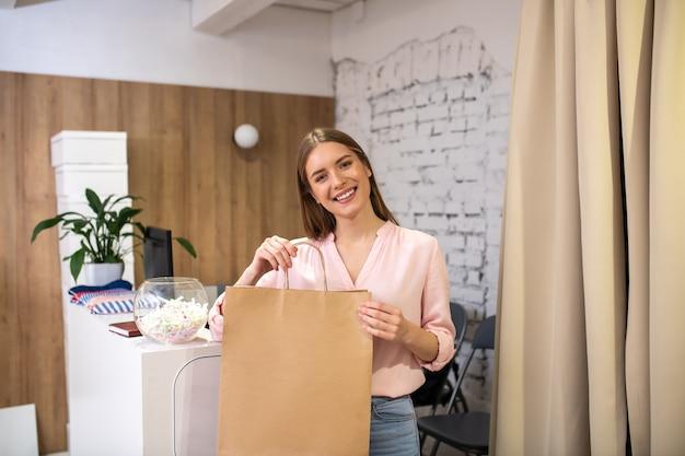 고객에게 포장 된 품목을주는 웃는 상점 관리자 프리미엄 사진