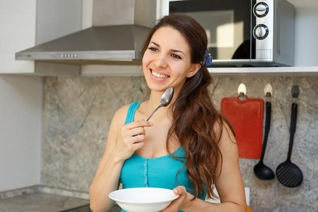 黒い髪と青いtシャツの笑顔の女性が彼女の手にスプーンを置いてキッチンに立っています。 無料写真