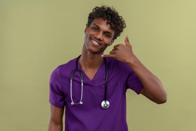 緑の空間で指で耳ジェスチャー電話記号の近くに手を握って聴診器で紫の制服を着た巻き毛の笑顔の若いハンサムな浅黒い医者 無料写真