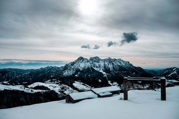 Заснеженный домик с прекрасным видом на заснеженные горы. Бесплатные Фотографии