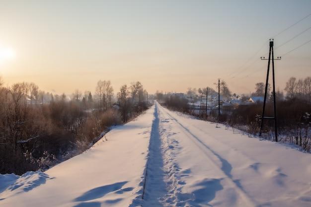 雪に覆われた鉄道と、冬に人々が踏む小道。たくさんの雪。 Premium写真