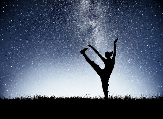 새벽 스포츠 소녀는 요가에 종사하고있다. 별이 빛나는 하늘에서의 휘트니스 교실 무료 사진