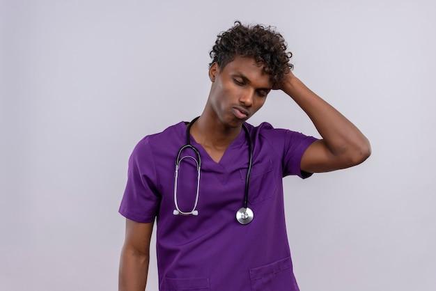 目を閉じて頭に手を当てている聴診器で紫の制服を着た巻き毛の重点を置かれた若いハンサムな浅黒い医者 無料写真