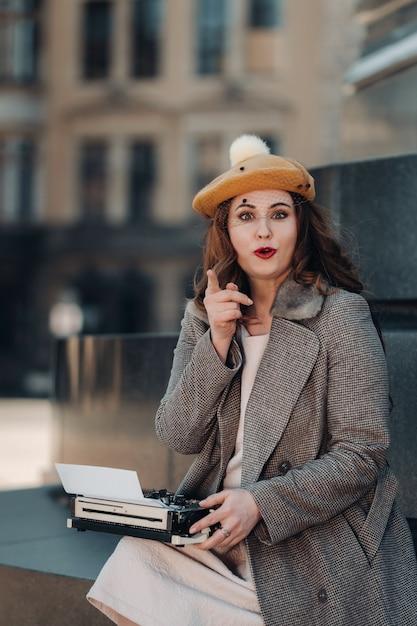 スタイリッシュな若い美しい女の子がドレスデンの旧市街に座って入力しています。ドイツ。 Premium写真