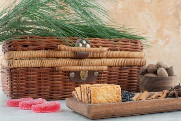 大理石の背景にクラッカー、スターアニス、シナモンスティックでいっぱいのスーツケースと木の板。高品質の写真 無料写真