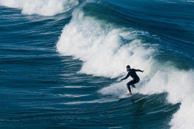 美しい波と海でサーフィンをするサーファーの男 無料写真