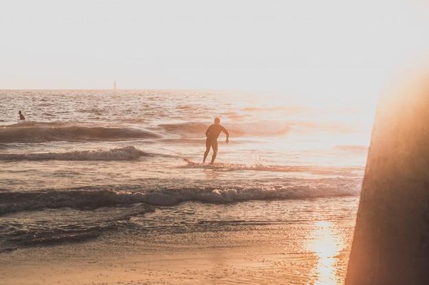 ビーチで走っているサーファー 無料写真
