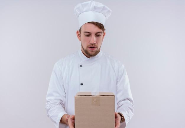 配達ボックスを保持し、白い壁でそれを見て白い制服を着た驚いた若いひげを生やしたシェフの男 無料写真