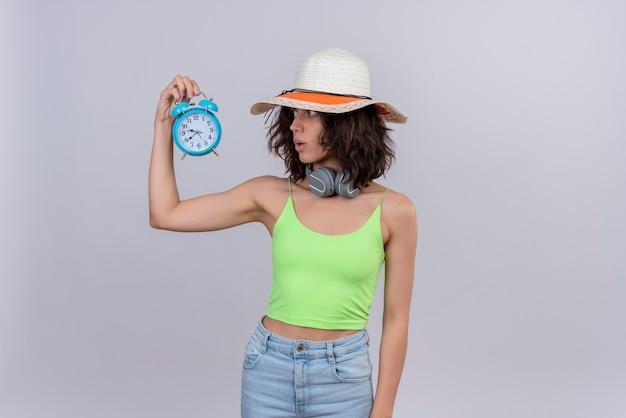Удивленная молодая женщина с короткими волосами в зеленом топе в шляпе от солнца смотрит на время, держа синий будильник на белом фоне Бесплатные Фотографии