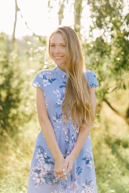 꽃과 긴 금발 머리와 파란 드레스에 달 콤 하 고 아름 다운 젊은 웃는 여자. 프리미엄 사진