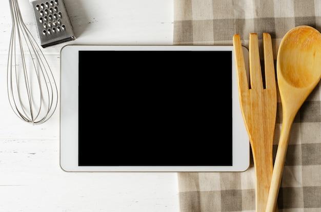 Планшетный компьютер и кухонный аккумулятор на белом деревянном Premium Фотографии