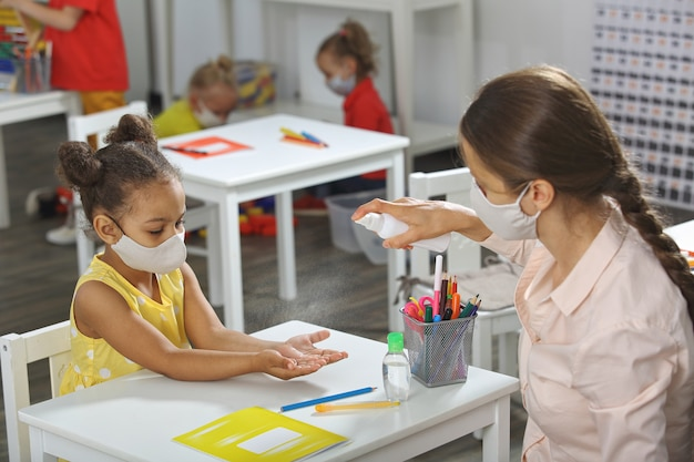 教師は、アフリカ系アメリカ人の生徒が教室で手で消毒するのを手伝います。 Premium写真
