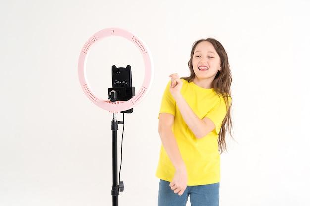 Девушка-подросток танцует и снимает видео. селфи. телефон установлен на штатив, светится кольцевая лампа. эмоции восторга и радости на лице ребенка. Premium Фотографии