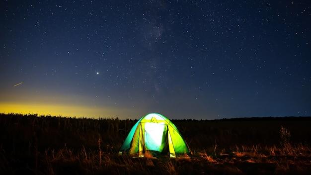 몰도바의 빛나는 별들로 가득 찬 하늘과 빛이있는 들판의 텐트 프리미엄 사진