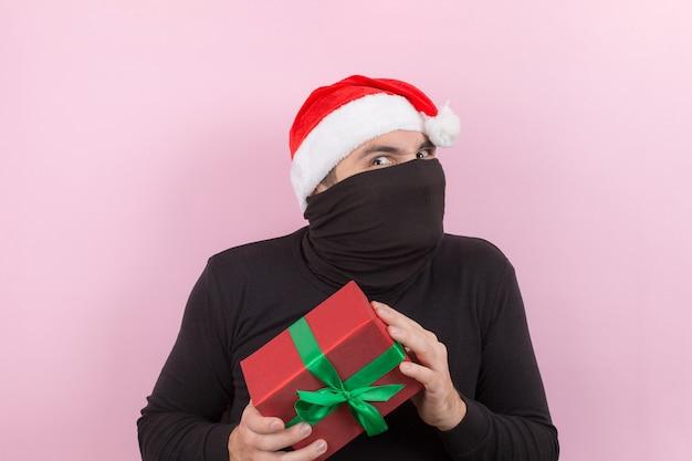 Вор в красной шляпе украл чужие рождественские подарки. злой характер, негативные человеческие эмоции. розовый фон, копия пространства. Premium Фотографии