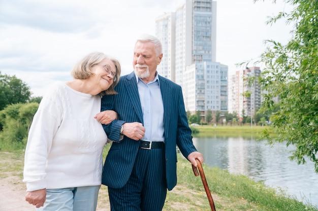 スタイリッシュな杖を持った思いやりのある老夫婦が新鮮な空気の公園を散歩します。 Premium写真