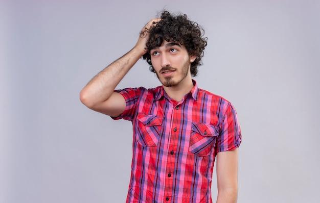 頭に手をつないでチェックシャツの巻き毛を持つ思いやりのあるハンサムな男 無料写真