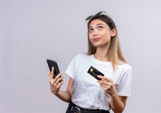 携帯電話とクレジットカードを持って考えながらサングラスをかけた白いtシャツの思いやりのある若い女性 無料写真
