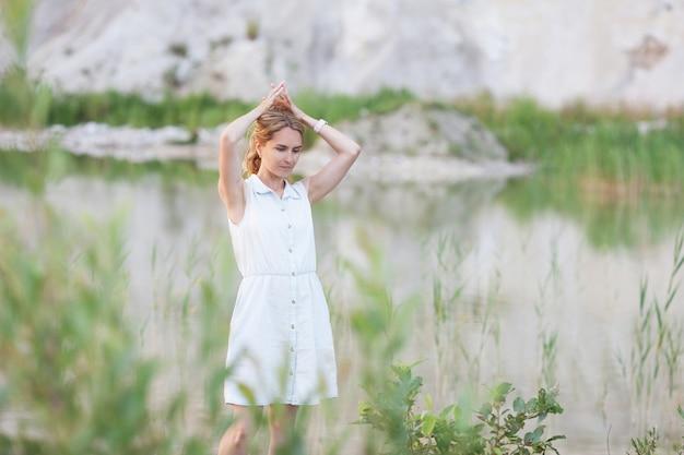 明るい砂丘を背景に湖に立っている思いやりのある若い女性。 Premium写真