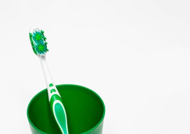 歯ブラシは白地にガラスの緑で、テキストの余地があり、歯を磨き、口の世話をします。 Premium写真