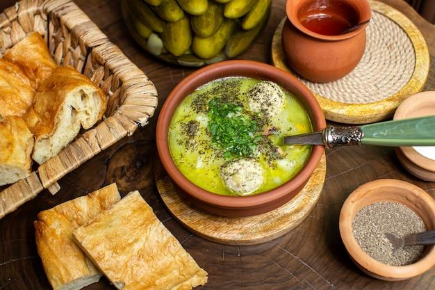 Вид сверху, горячий суп в коричневом круглом горшочке, нарезанный соленый огурец, хлеб и специи Бесплатные Фотографии