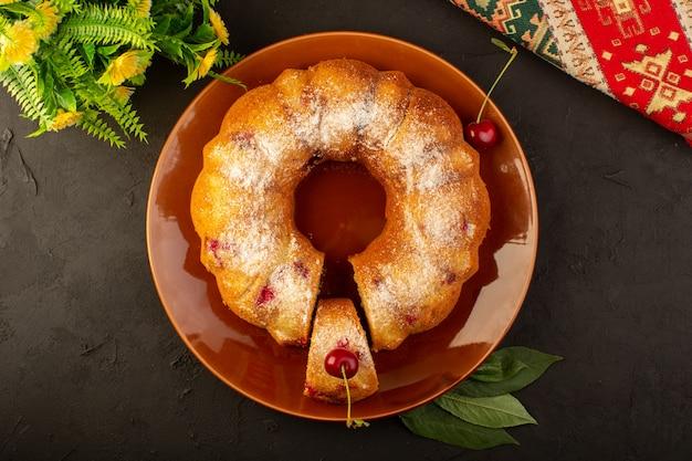 Вид сверху запеченный фруктовый торт вкусный круглый с красной вишней внутри и сахарной пудрой внутри круглой коричневой тарелки на темном Бесплатные Фотографии