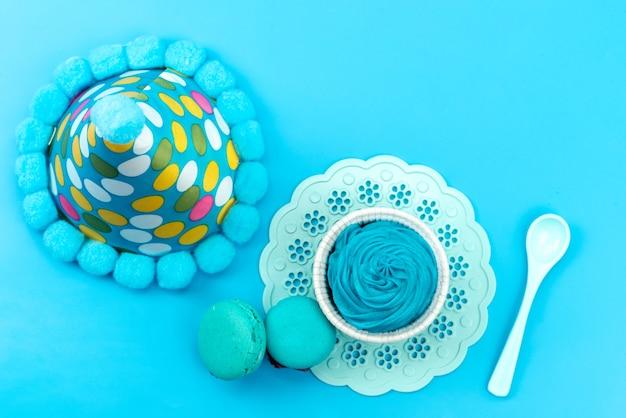 トップビューブルーフレンチマカロンと青いデザートホワイトプラスチックスプーン、青い机の上の誕生日キャップ、誕生日パーティー 無料写真