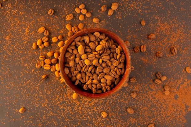 茶色のテーブルの上の茶色のプレート内のトップビュー茶色のコーヒー種子 無料写真